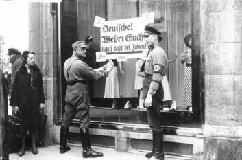 """Berlin 1933: Nazister henger opp et skilt med teksten: """"Tyskere, forsvar dere, ikke kjøp hos jøder"""" på et jødisk butikkvindu. (Foto: Deutsches Bundesarchiv / Wikimedia commons)"""