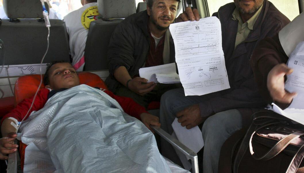 En palestinsk gutt ligger på ei båre mens familien viser tillatelsene sine til journalister. Familien er på vei til et sykehus i Israel igjennom grenseposten ved Erez i den nordlige delen av Gaza-stripa, 27. november 2008. (AP Photo/Adel Hana/SCANPIX)