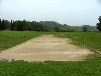"""""""Rundt 1960 oppdaget tyske arkeologer stadionet i Olympia. Løpebanen er 192,28 meter lang, og i følge myten brukte Herkules lengden av sin fot 600 ganger for å måle opp denne distansen. Det var det tredje stadionet grekerne bygde til Olympia, men er likevel så gammelt som fra det femte århundret f.Kr. I OL 2004 ble kulekonkurransene for begge kjønn lagt hit til denne mest opprinnelige Olympiastadion. (Foto: ATHOC/ANA/C. Constantopoulos)"""""""