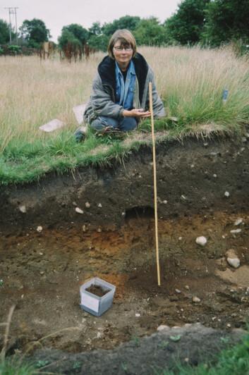 Botaniker Eli-Christine Soltvedt sitter ved et felt for arkeologisk utgraving. (Foto: Terje Tveit)