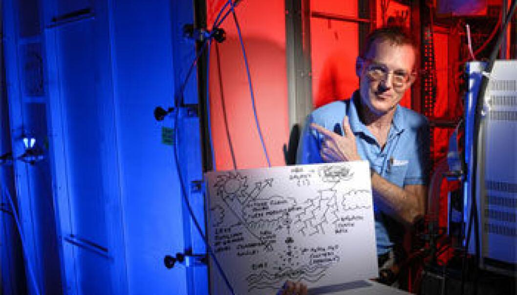 """""""Jasper Kirkby ved CERN foran CLOUD-prototypen. Han holder en skisse som forklarer den mulige forbindelsen mellom kosmiske stråler og skydannelse."""""""