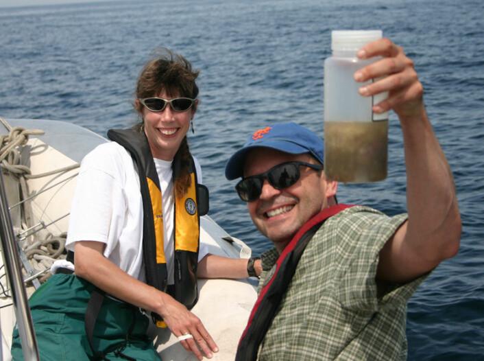 Joe Roman fra University of Vermont holder opp en prøve av avføring fra hval. I bakgrunnen forskeren Becky Woodward. (Foto: Jeremy Winn)