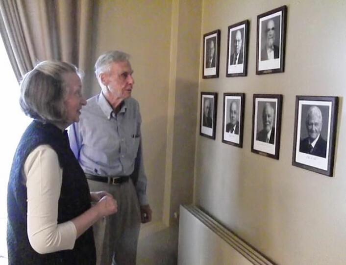 Carol og John Tate ved portrettveggen av Abelprisvinnere, Abelrommet i Vitenskapsakademiet. (Foto: Arnfinn Christensen)