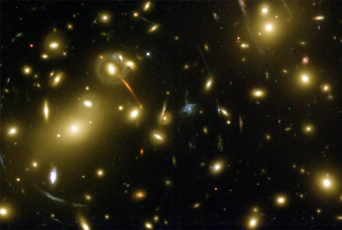 Mørk materie er hittil bare blitt observert indirekte, for eksempel ved at det bøyer av lys som passerer forbi det på sin vei gjennom rommet. Det fenomenet kan man se på bildet under, hvor den mørke materien i galaksehopen Abell 2218 bøyer av lys fra fjernere galakser, som dermed blir forvrengt (de lange, lysende strekene). (Foto: NASA)