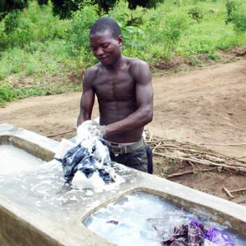 Chimwemwe Douglas vasker klær i de nye vaskene. – Vær så snill å fortell dem at vi trenger flere brønner, sier han. (Foto: Teresa Grøtan)