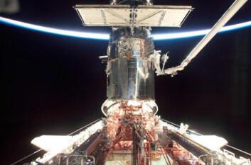 """""""Hubble repareres i 2002, med jordkloden som kommer frem i lyset i bakgrunnen. En astronaut jobber med halve kroppen inne i romteleskopet."""""""