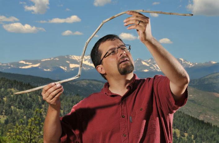 Forsker Craig Lee holder et 10 000 år gammel spyd i hendene. Spydet ble funnet i en smeltende flekk med permanent snø i Rocky Mountains. Det har blitt bøyd og nesten brukket mens det har ligget i isen, men er ellers godt bevart. (Foto: Casey A. Cass/University of Colorado)