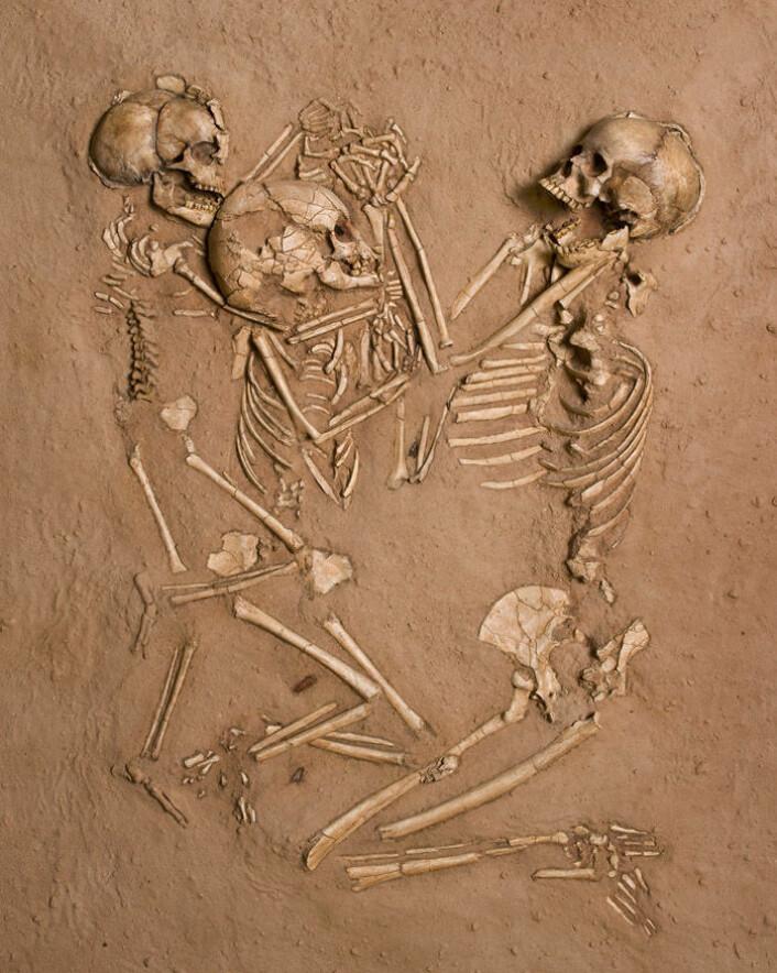 En underlig trippelbegravelse fant sted i Gobero for rundt 5 300 år siden. En vever kvinne og to barn på fem og åtte år ligger med armene flettet sammen. Sanda under de tre er full av pollen. Det tyder på at de tre ble lagt til hvile på en seng av blomster. Ingen av skjelettene bærer noen tegn på skade. (Foto: Mike Hettwer, Project Exploration)