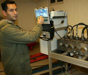 I en låvekjeller: Mohammed Hoseini med en multiblokk - seks enheter som kan overvåke samme maskin og opereres online med PC og mobil. (Foto: Trond Solem)