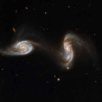"""""""Romteleskopet har fanget galaksene i det som kan minne om en dans. Begge inneholder ekstremt massive, sorte hull, og det foregår intens stjernedanning. Galaksene er omlag 300 millioner lysår unna. (Foto: NASA/ESA)"""""""