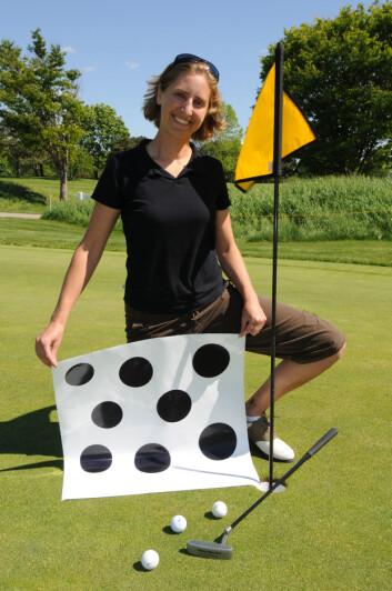 """""""Forsker Jessica K. Witt med plansjen hun viste til 46 golfere. De som var flinkest til å putte, var også de som oftest trodde at golfhullet er større enn det i virkeligheten er. (Foto: David Umberger/Purdue University)"""""""