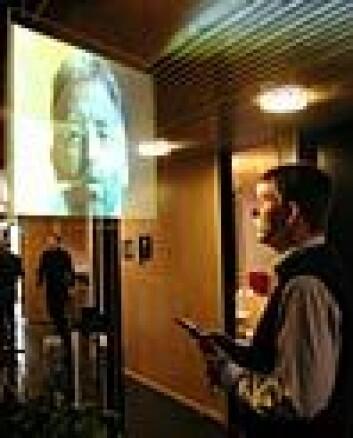 """""""Lars Svenkerud i Telenor FoU viser hvordan en gjennomsiktig skjerm kan brukes til å formidle videobeskjeder. Skjermen kan blant annet aktiveres via mobiltelefon."""""""