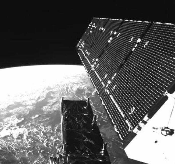 Sentinel-1A i bane, med det ene solpanelet i øvre del av bildet. Nederst ses oversiden av radarantennen. I bakgrunnen ses en ganske kjent planet. (Foto: (ESA))