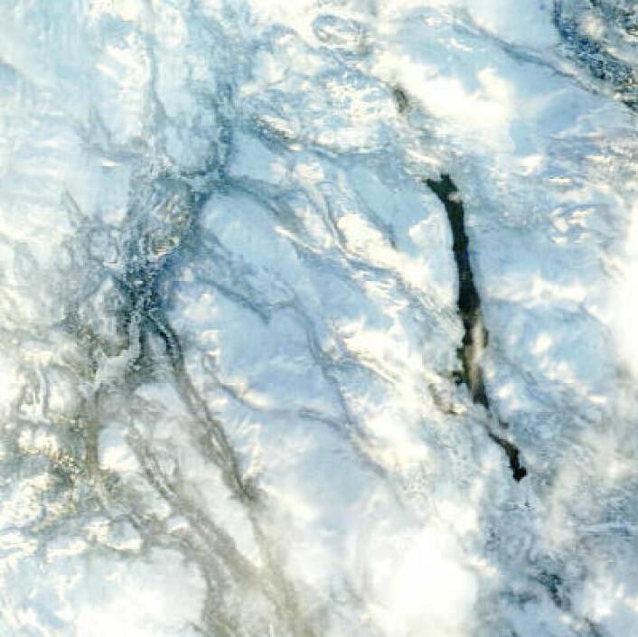 En isfri Femunden skimtes gjennom skyene 29. desember i dette bildet fra NASAs satellitt Terra. Temperaturen ved Drevsjø har vært 6 grader høyere enn normalen for desember. (Foto: (NASA Terra MODIS))
