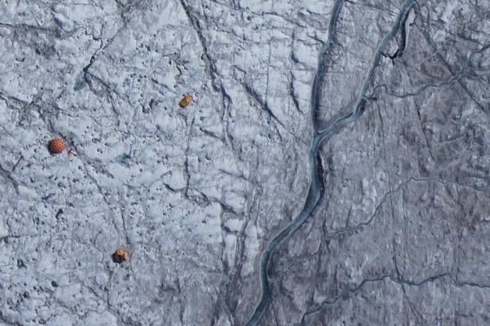 Dronebilde av teltene og det vitenskapelige utstyret på isen i Grønland. Den mørke isen, rik på urenheter, er særlig godt synlig øst for smelte-elven nært leiren. (Foto: J.Ryan / J.Box / A.Hubbard)