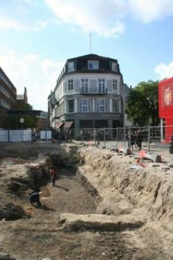 Bildet viser det opprinnelige gatebelegget, som ligger samme sted som dagens Overgade. Litt bak arkeologen som kneler, ble det første kattefunnet gjort. (Foto: Odense Bys Museer)