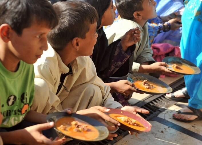 WHO anslår at under 9 prosent av verdens befolkning nå er undervektige. Disse barna får delt ut mat utenfor en restaurant i Karachi i Pakistan. Mer enn fire ganger så mange – nesten 40 prosent av verdens befolkning – er overvektige. Av disse har over 13 prosent fedme. (Foto: Rizwan Tabassum/AFP/NTB scanpix)