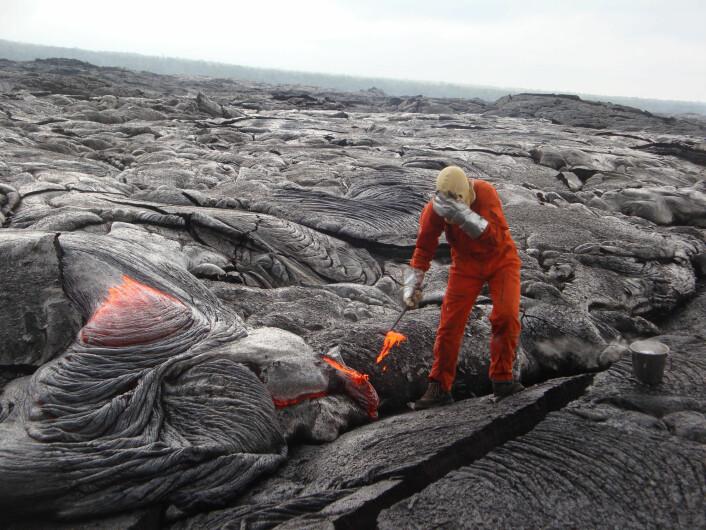 Ein geolog frå HVO skjermar ansiktet frå den intense varmen i det han tek ein prøve frå lavaen frå Kilauea, 21.oktober 2013. (Foto: U.S. Geological Survey, Hawaiian Volcano Observatory)