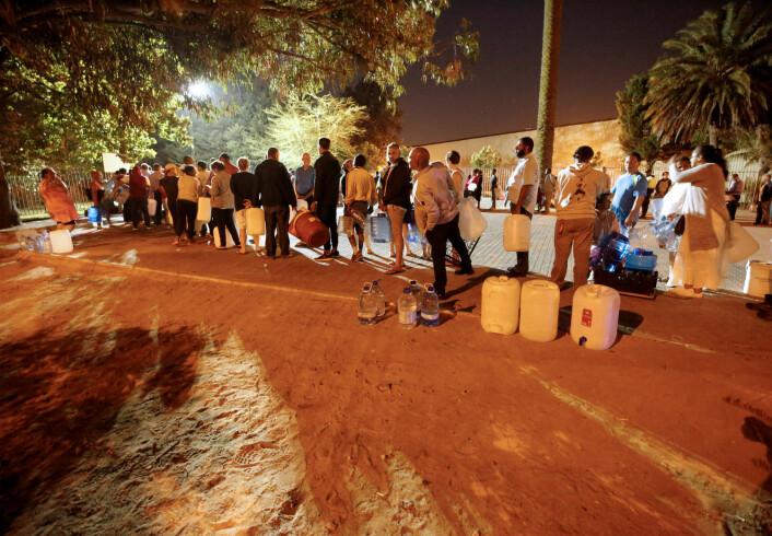 Folk står i vannkø i Cape Town. Dette bildet er tatt i slutten av januar, og i noen deler har byen har folk allerede måttet stå i vannkø. (Bilde: REUTERS/Mike Hutchings/NTB Scanpix)
