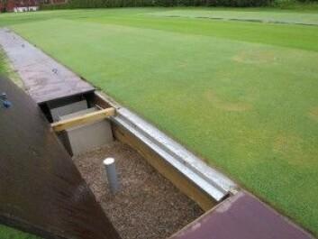 Disse grøftene gjør det mulig å samle opp vannet som renner gjennom greenen. Vannet fra de ulike forsøksfeltene samles opp i separate tanker og kan så analyseres for å undersøke om det inneholder rester av plantevernmidler. (Foto: Marit Solum)