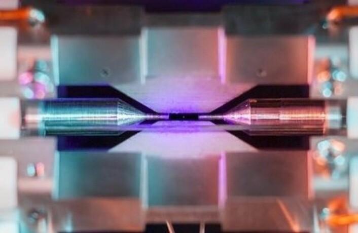 Her kan du skimte den ørlille prikken av et strontium-atom der det ligger badet i blå-fiolett laserlys og i spenn i det elektriske feltet mellom de to elektrodene. Strontium-atomer som dette blir brukt i supernøyaktige atomklokker. (Foto: David Nadlinger ved University of Oxford)