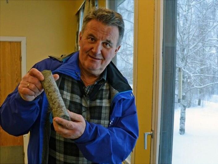 Forsker Jan Steinar Rønning viser fram en kjerneprøve med fargerike innslag av sjeldne jordartsmetaller. (Foto: NGU)