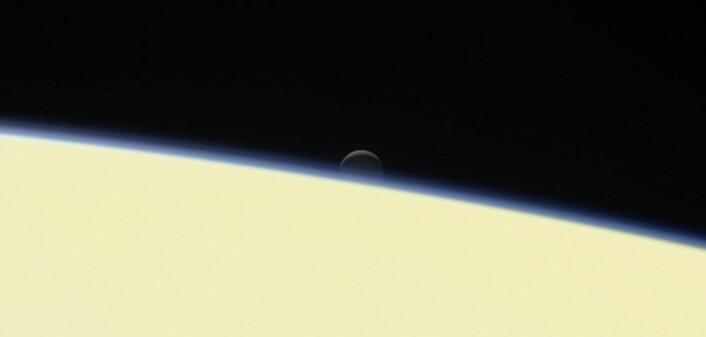 Den lille månen Enceladus går ned bak Saturn. Bildet er tatt av Cassini den 13. september, bare to dager før romsonden brant opp i de øvre lagene av Saturns tykke atmosfære. (Foto: JPL/NASA)