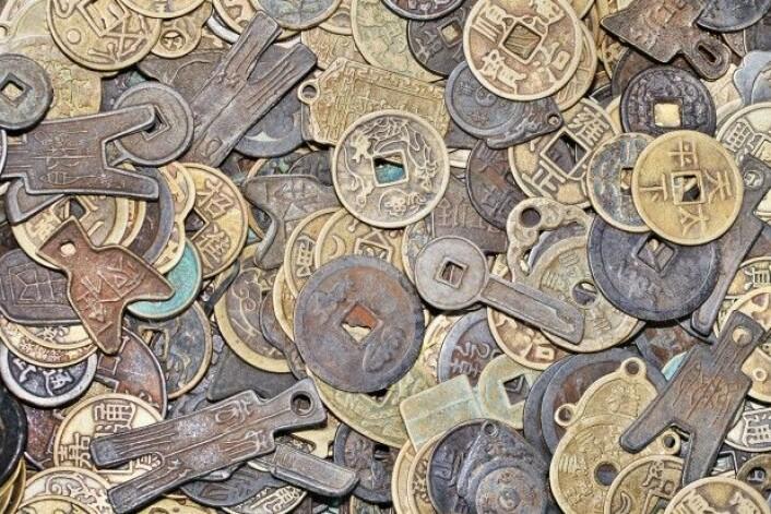 Det er ikke noen regel som sier at mynter må være runde. Her er det en samling av gamle kinesiske mynter i ulike former og farger. (Foto: TonyV3112 / Shutterstock / NTB scanpix)