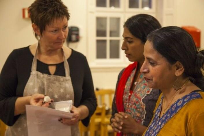 Monica Morris (til høyre) kom til Norge fra India for 20 år siden. Hun er en av kursholderne i Bønner virker. Hennes kollega Anica Munir (i midten) svarer kursdeltaker Sigrun Blixtad (til venstre) som lurer på hvordan hun best kan lage linse-paroka, som er grønnsakssnacks fra India. (Foto: Tove Rømo Grande/NMBU)