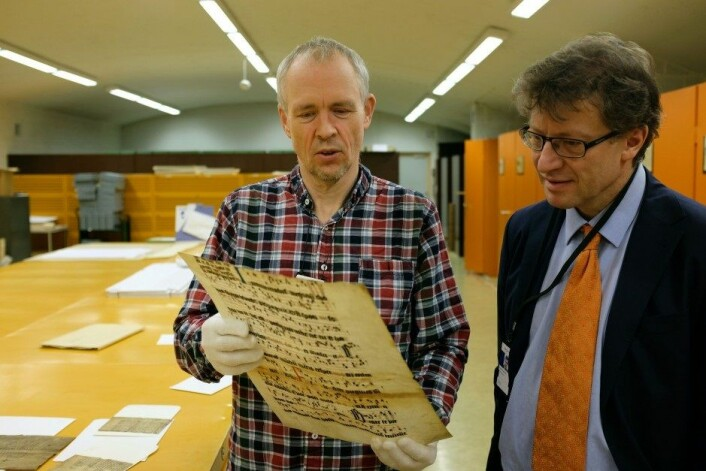 Tor Weidling (t.v.) og Espen Karlsen samarbeider om å finne gamle dokumentfragmenter. Dokumentet her er fra 1300-tallet. (Foto: Silja Björklund Einarsdóttir/forskning.no)
