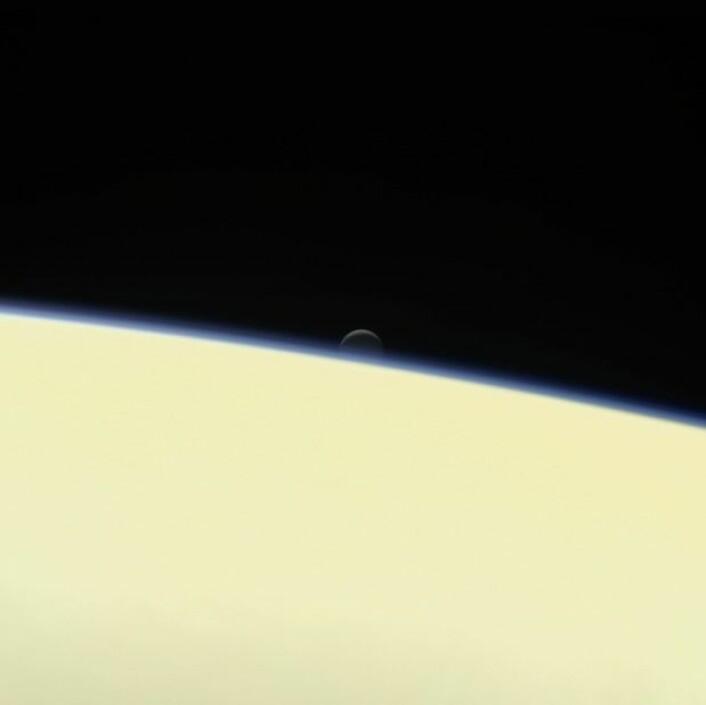 Månen Enceladus synker ned bak den store gassplaneten Saturn på dette portrettet tatt av Cassini 13. september, få dager før fartøyets endelikt. (Foto: Nasa)