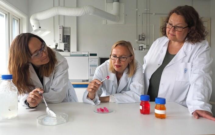 Forskerne Ellinor Bævre Heggset (fra venstre), Kristin Syverud og Ingebjørg Leirset viser frem nanocellulose-byggesteinene i vann. De rosa klumpene er stillaser (scaffolds) for celler bygget av disse byggesteinene. (Foto: Per Olav Johnsen / RISE PFI)