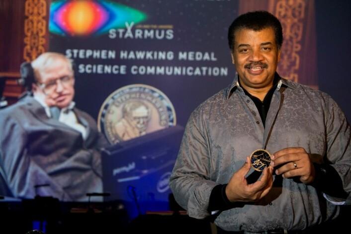 Neil deGrasse Tyson med Stephen Hawking-medaljen for forskningsformidling. I bakgrunnen på storskjerm: Stephen Hawking selv. (Foto: Max Alexander, Starmus)